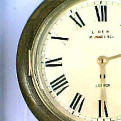 Fake fusee dial clock with a bezel hinge on the left and bevelled glass